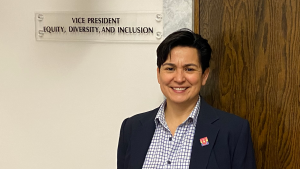 "Mary Ann Villarreal poses for photo in front of sign reading, ""vice president, Equity, Diversity, and Inclusion"""