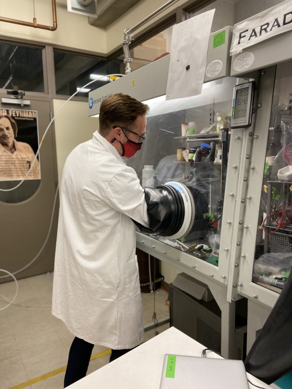 a caucasian man wears a lab coat and a mask and has his arms in protected gloves doing something in a machine.
