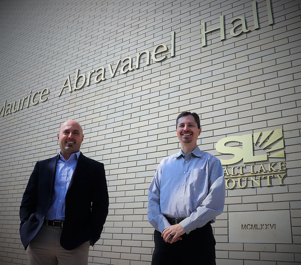 two engineers stand in front of the building where the symphony performs in salt lake city.