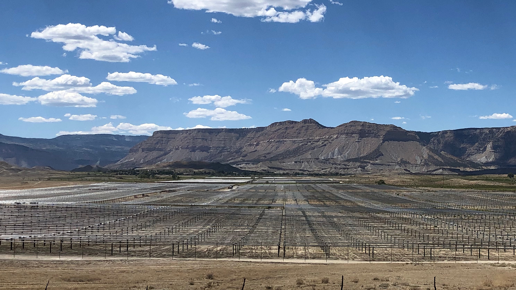 landscape photo of DESRI's Hunter Solar site in Emery County, Utah set against mountains and blue sky