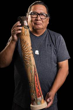 A Native American man with black framed glasses holds up his hand carved corn maiden kachina The kachina is a long, wooden figure of a women—the top is her head, and the rest is her body, represented as a long cylindrical cloak painted as a cloak.