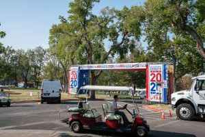 a volunteer sits in a golf cart waiting to provide rides around the VP debate grounds