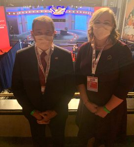 Rebecca Schwartz poses for photo inside the debate hall with Utah Governor Gary Herbert. both wearing masks. Debate hall stage in the background.