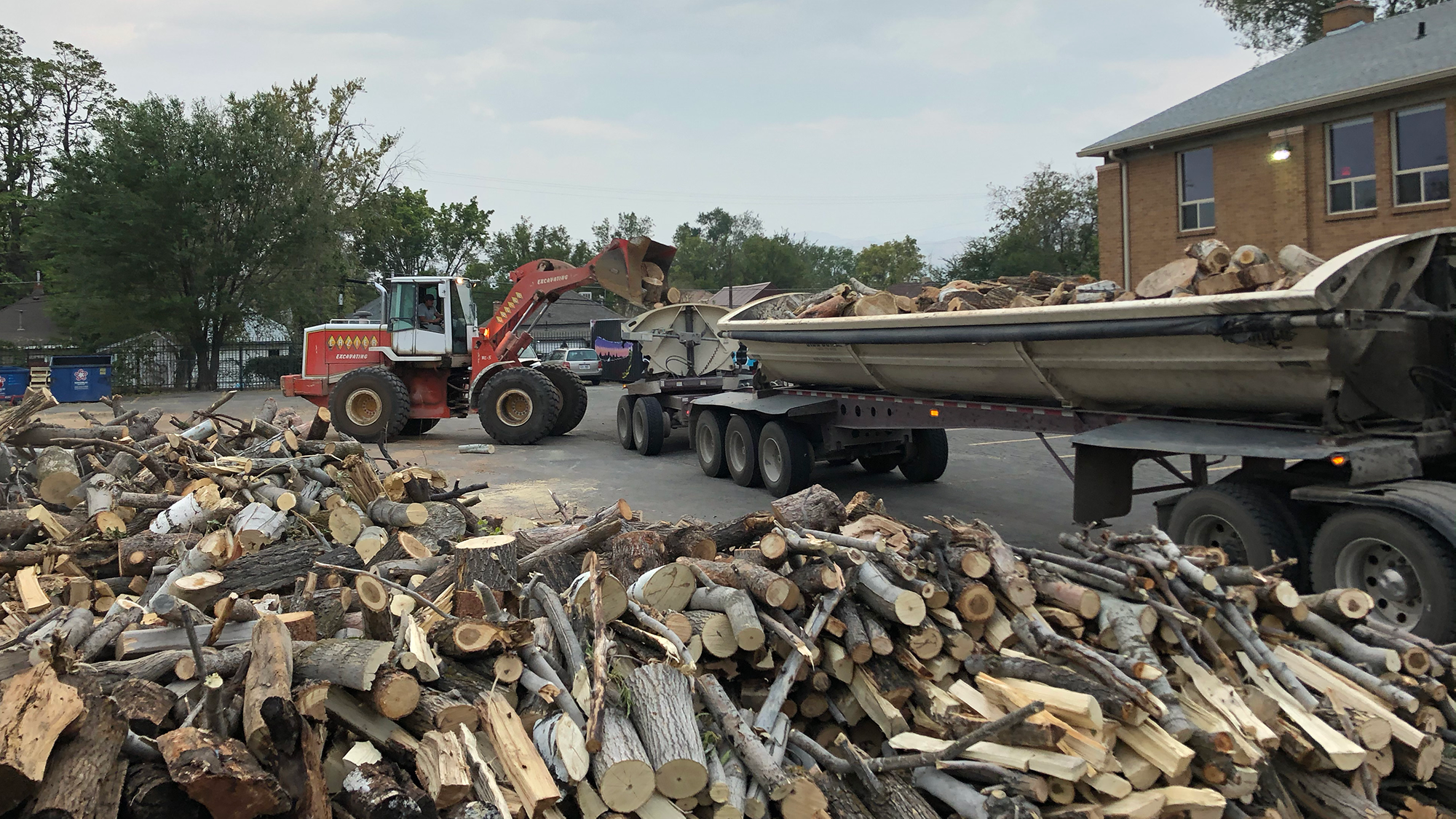 an 18-wheel truck bed is loaded with firewood and is parked next to a large pile of more firewood