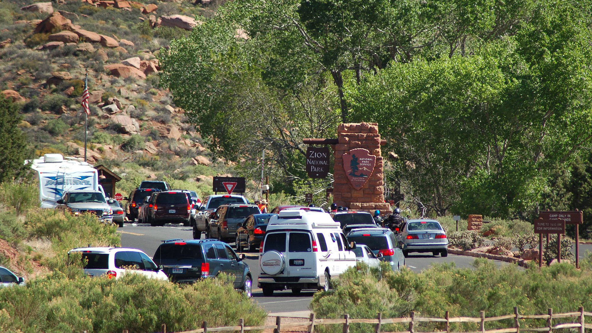 A massive line of cars wait in traffic to enter Zion National Park in the southern part of Utah in the United States. Midway in the line of traffic is a sign with the park's name on it. In the background is a cliff of red rocks that the region is known for. Green trees tower over the cars.