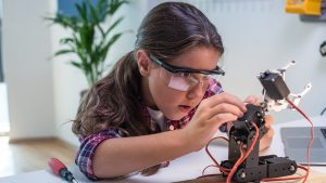 young student wearing safety goggles tinkers with small robotic hand.