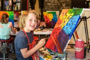 young student paints on a canvas