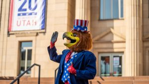 The U's mascot, Swoop, dressed in red, white, and blue waves to crowd.