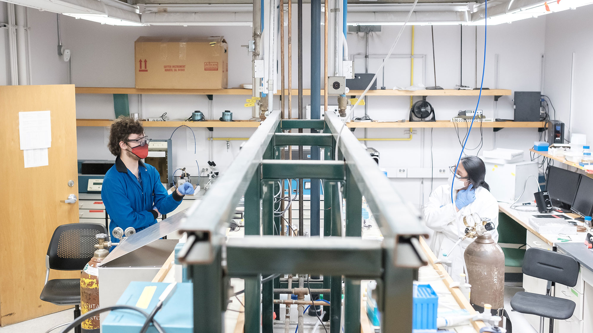 A laboratory, the camera looking down from above. A long beam bisects the center of the photograph, with a lab bench on either side. On the right is Angus Wu, an asian student in a lab coat, face covering, and gloves. On the left is Andrew Pendergrast, a white man wearing a blue lab coat, face covering and gloves.