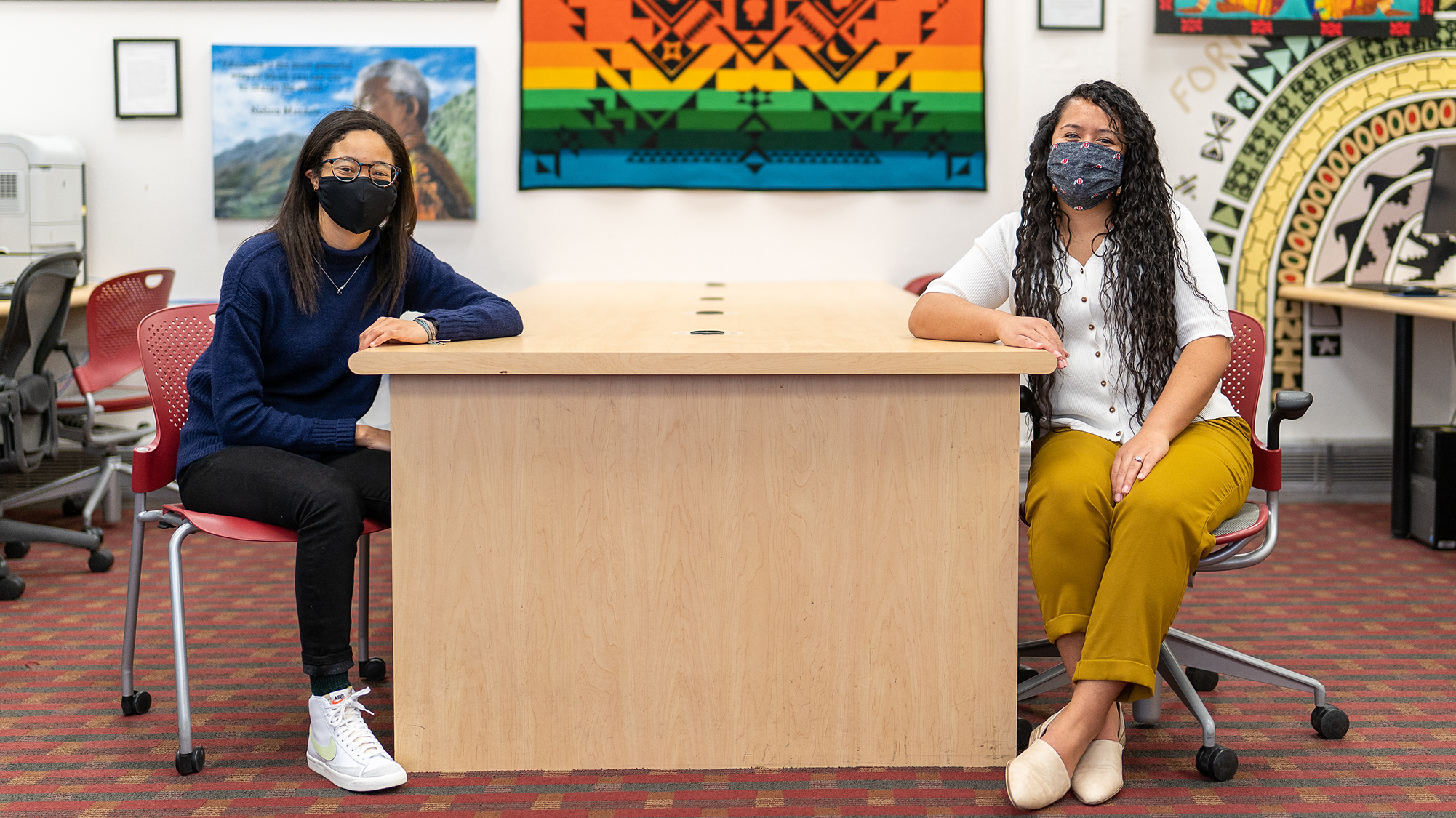 two women sit across table from one another wearing masks, facing camera.