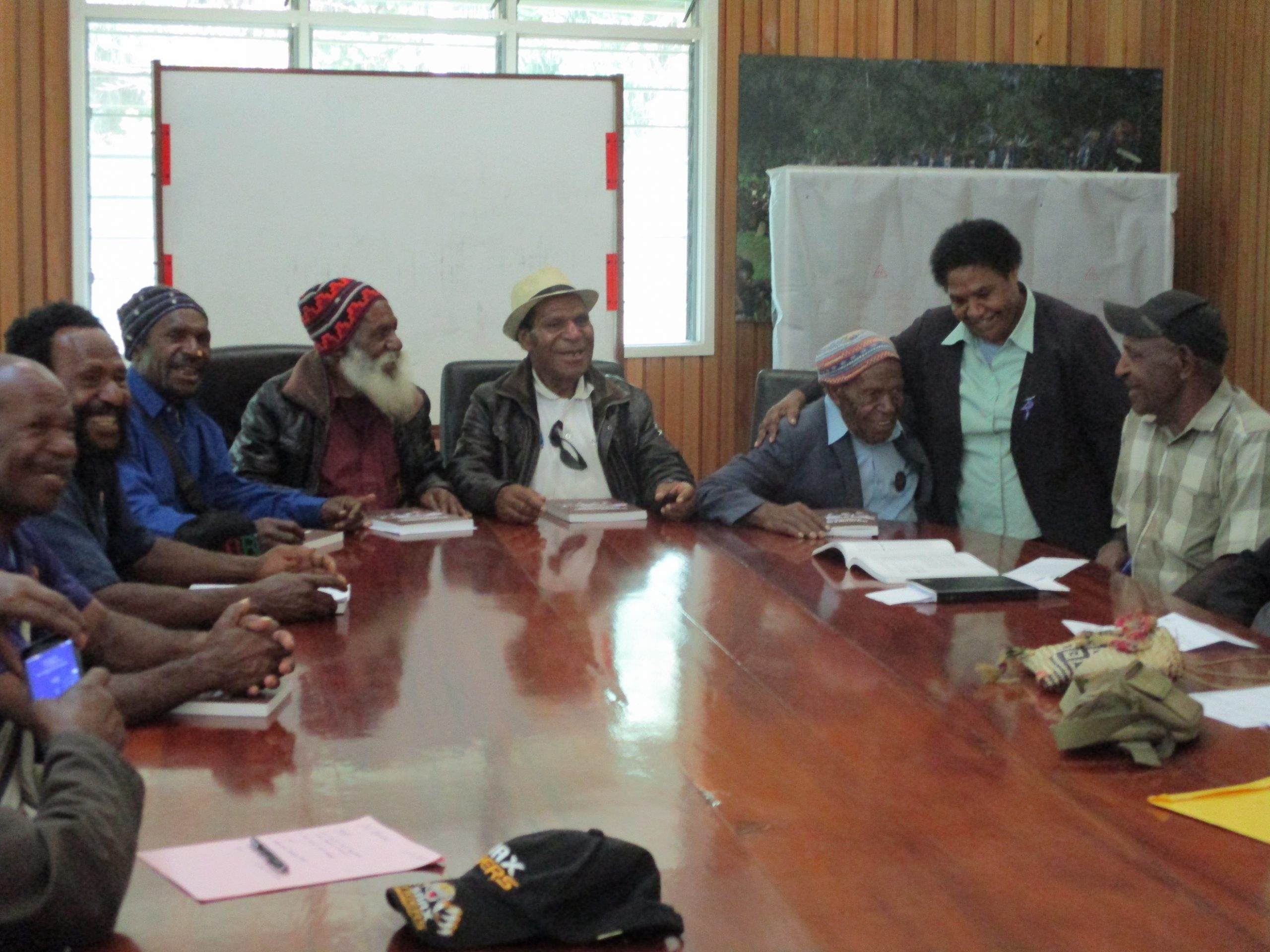 A group of magistrates from the Enga of Papua New Guinea sit around a conference table with papers in front of them.
