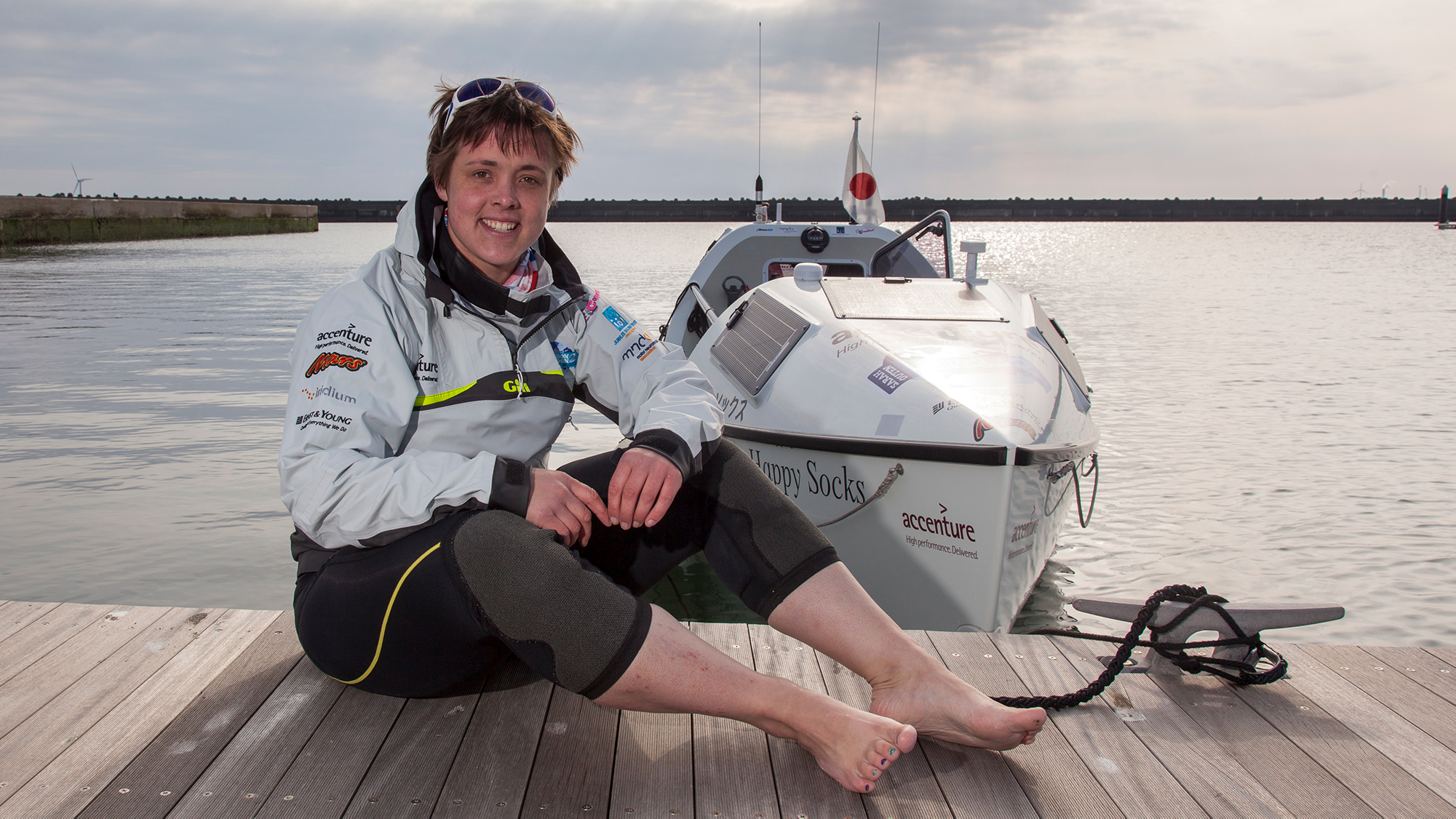 Sarah Outen sits on dock in front of kayak on the water