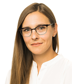 A headshot of Sarah Braden, a white woman with brown hair and glasses wearing a white shirt against a white background.