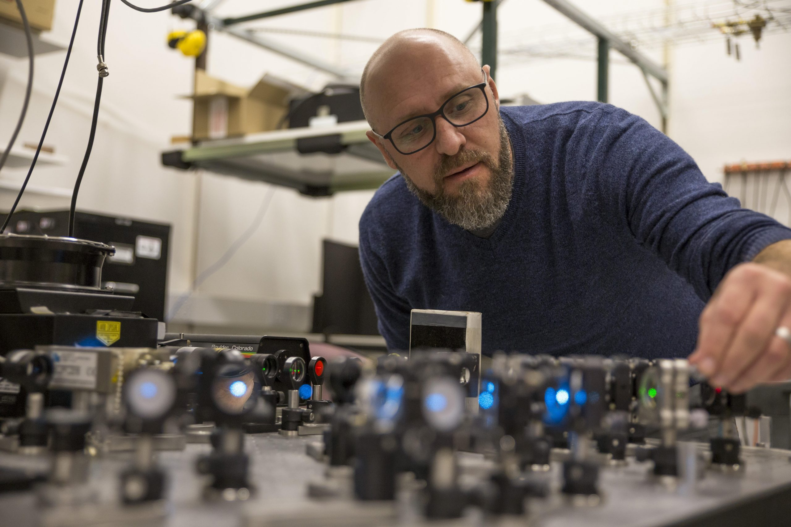 Jordan Gerton, a white male with a short-cropped beard and glasses, leans over an array of mirrors and lasers in his laboratory.