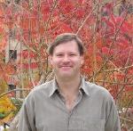 A headshot of John Matthews, a white man with brown hair wearing a tan shirt against fall leaves.