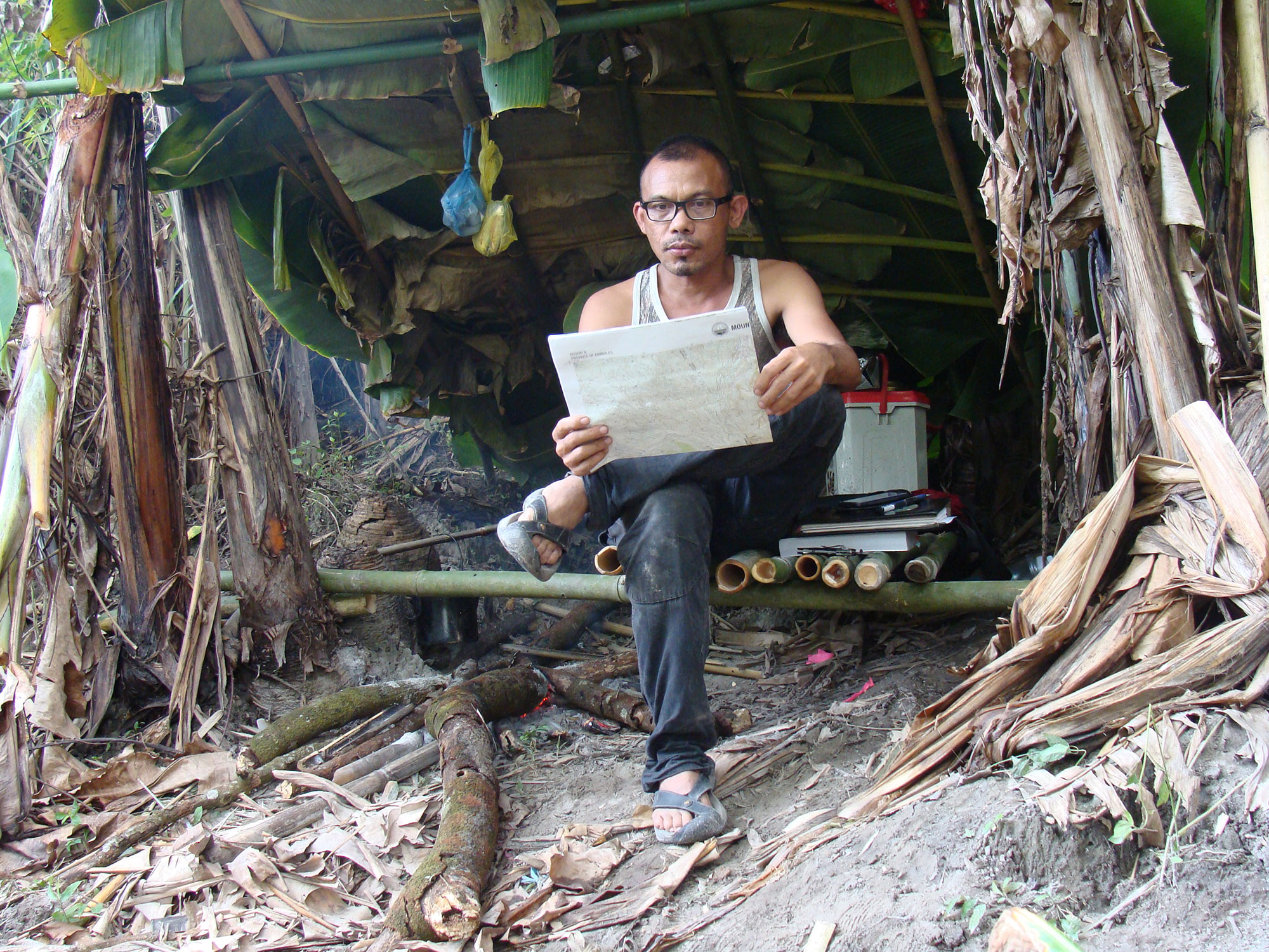 Filipino scientist Danny Balete sits under a shade made of palm leaves in the Philippines.