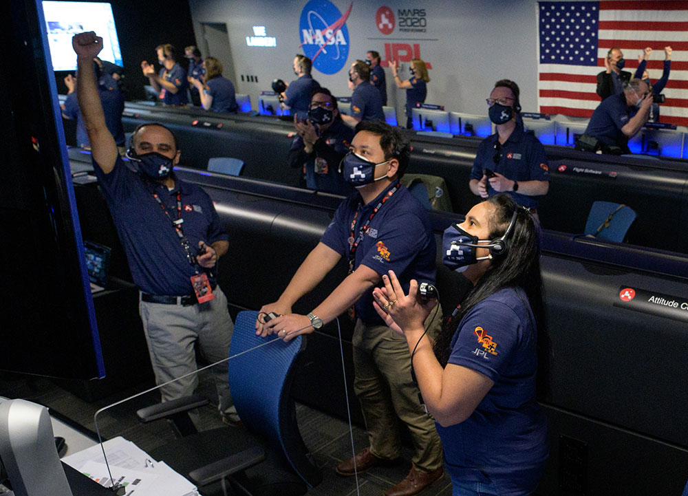 A group of scientists from NASA all stand staring at a screen outside the right of the frame, cheering and clapping awaiting news of the Perseverance Rover landing.
