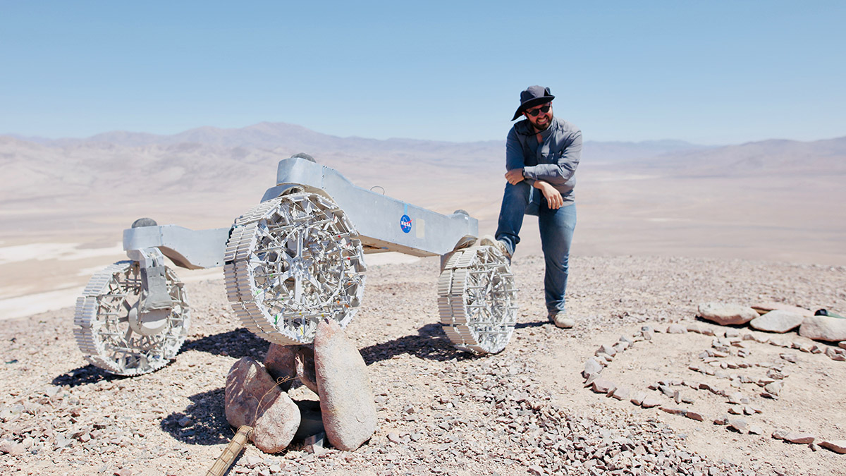 A man in a cowboy hat, jeans, button up shirt, stands with his right leg up on a rover, a silver vehicle with huge all-terrain wheels and a NASA logo, in a barren desert landscape - white sediment, light blue sky at the horizon, and blurry mountains very far away.