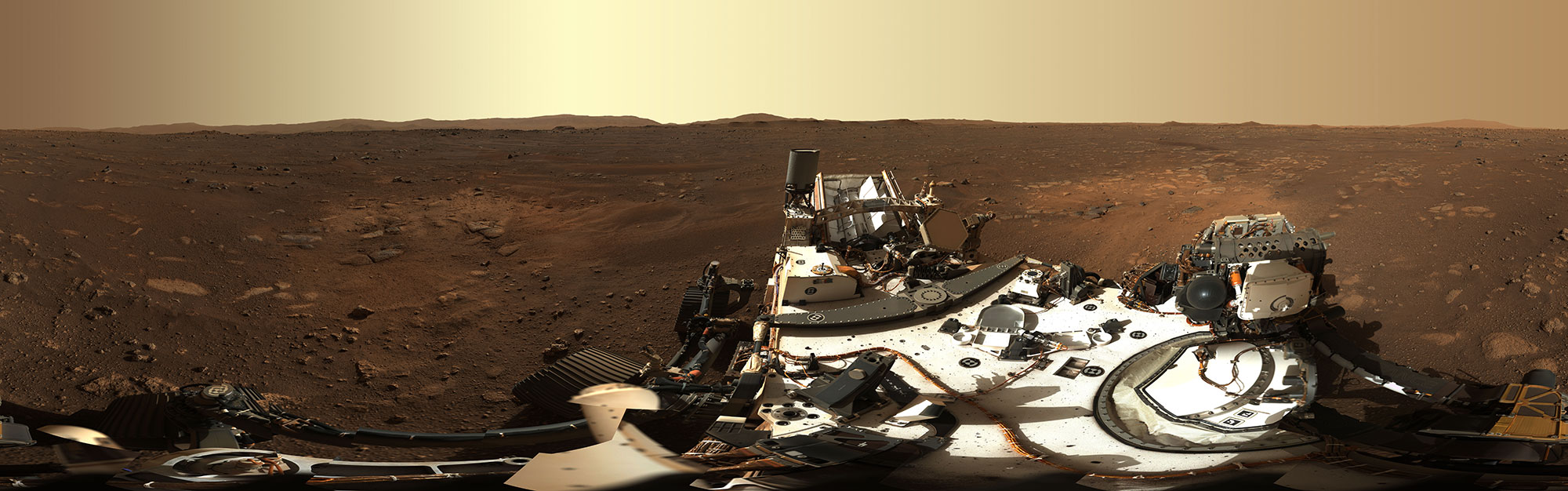 A 360 degree image of the rover, a silver robotic car-like craft, on Mars, a flat red dirt landscape.