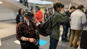 Two people with virtual reality glasses in a conference-like room with other people testing out VR glasses in the background.