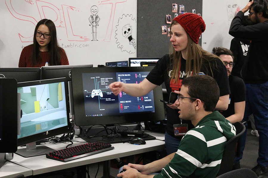 A woman in a red beanie and black shirt stands, discussing animation on a computer screen, to a male student sitting at the computer. He is wearing glasses and a long sleeved green and white striped shirt. She seems to be giving feedback.