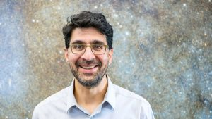 A headshot of Anil Seth, wearing glasses and a collared shirt, in front of a photo from a space telescope that shows millions of stars.