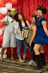 CESA graduates pose for photo with props in photo booth.