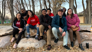 eight people pose for a photo outside sitting on some large rocks.
