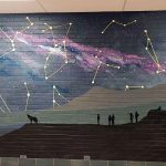 A mural of the night sky, with a full moon. Constellations are drawn in the sky, the sky shows an arm of the Milky Way galaxy in fuchsia and dark blue, the full moon shows a figure of a rabbit in it. The foreground is a silhouette of a hill with a wolf howling, people pointing at the sky. The bottom has numbers that show how the darkness gets lighter towards the city due to light pollution.