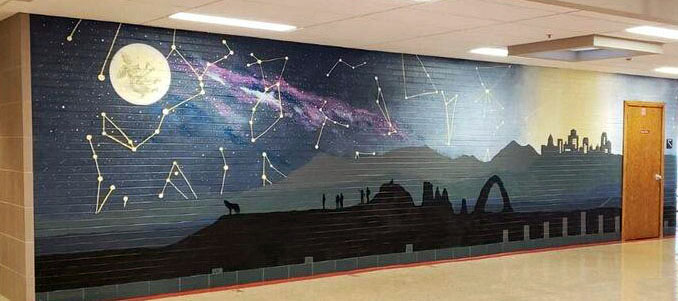 A full wall mural. From the left, the sky is dark and the stars and Milky Way are bright. There's a full moon with a figure our a rabbit in it. as the mural goes to the left, it gets closer to a city and the light pollution gets worse, obscuring the celestial bodies in the sky. There's a silhouette of a hill with a wolf and figures looking at the sky.