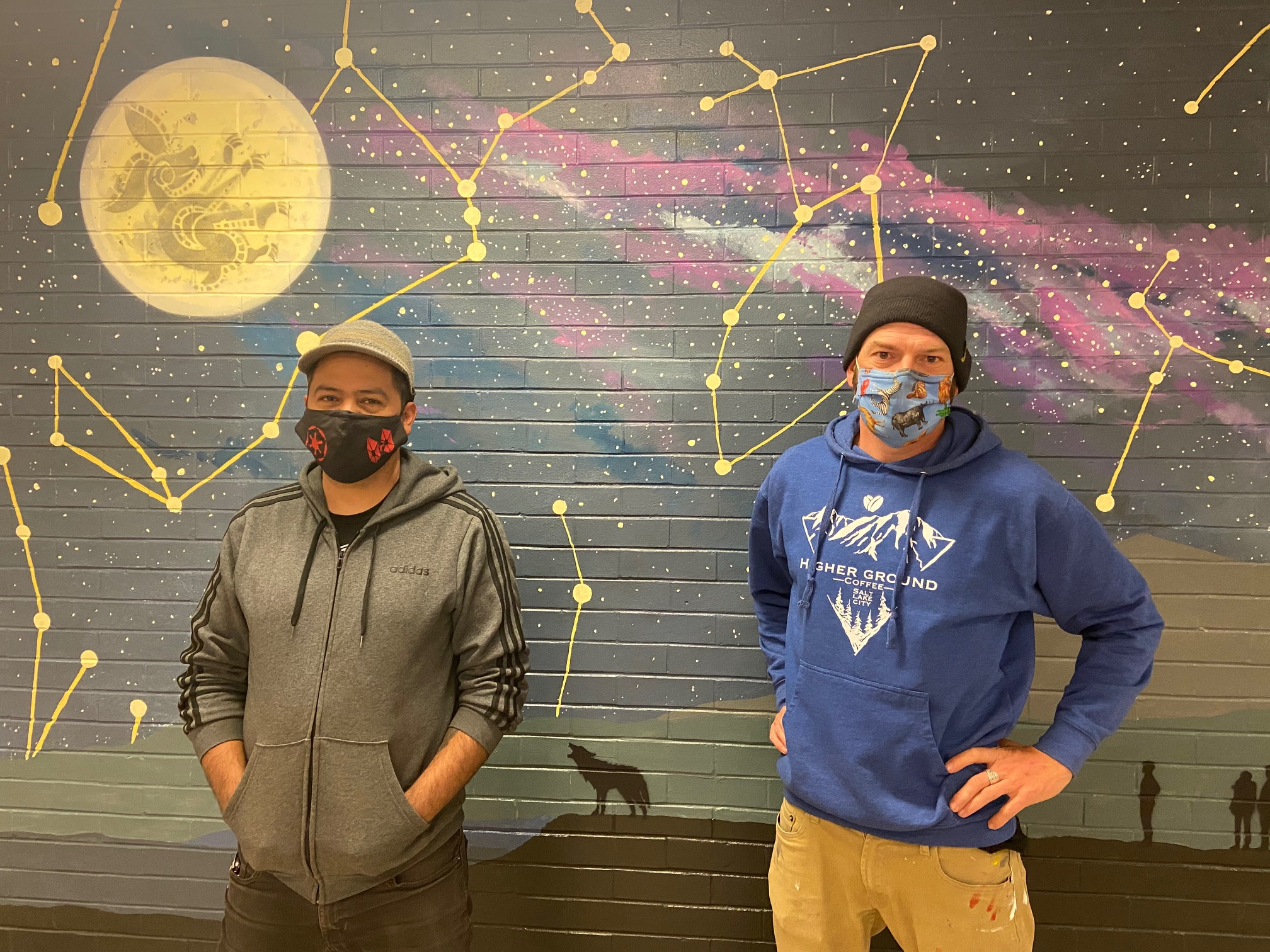 Jorge Arellano, left, wears a gray zip up hoodie, a gray hat and black jeans, and a mask. Josh Scheuerman, right, wears a blue sweatshirt, brown pants a black beanie and a mask. They stand in front of their mural.
