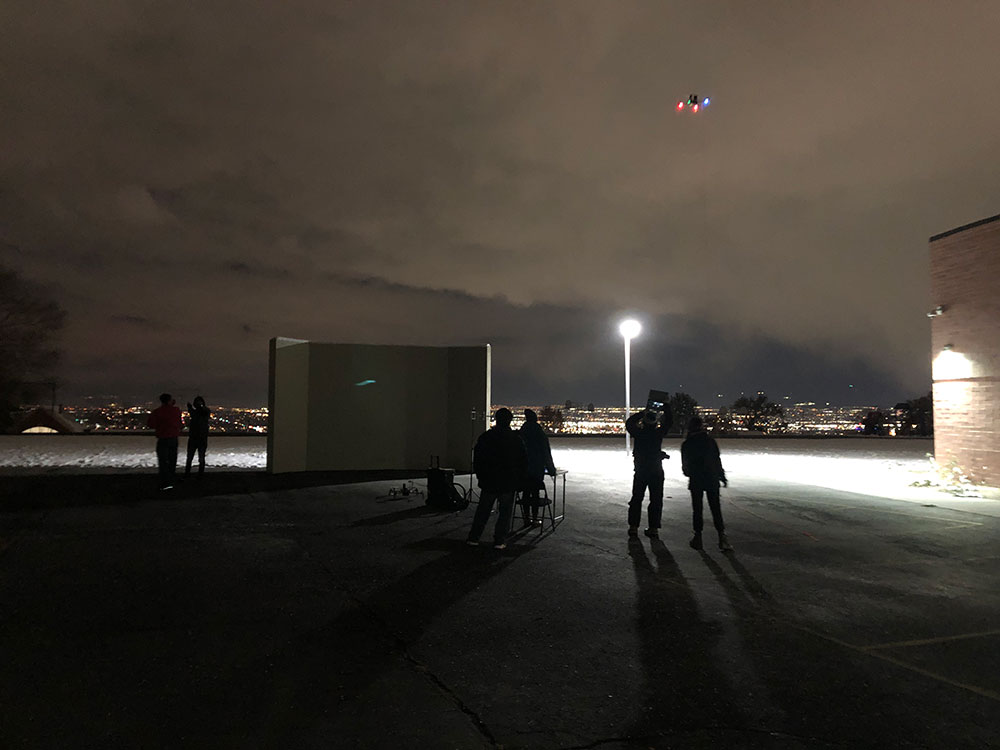 At night outside, six figures look up at an atonomous drone that's flying around a school taking brightness measurements. There's a very bright light, and beyond the school there are the bright lights on the city. The sky is cloudy.
