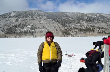 A woman scientist stands on a frozen lake in a yellow life vest, a red beanie, with hills in the background. Equipment is seen in the background.