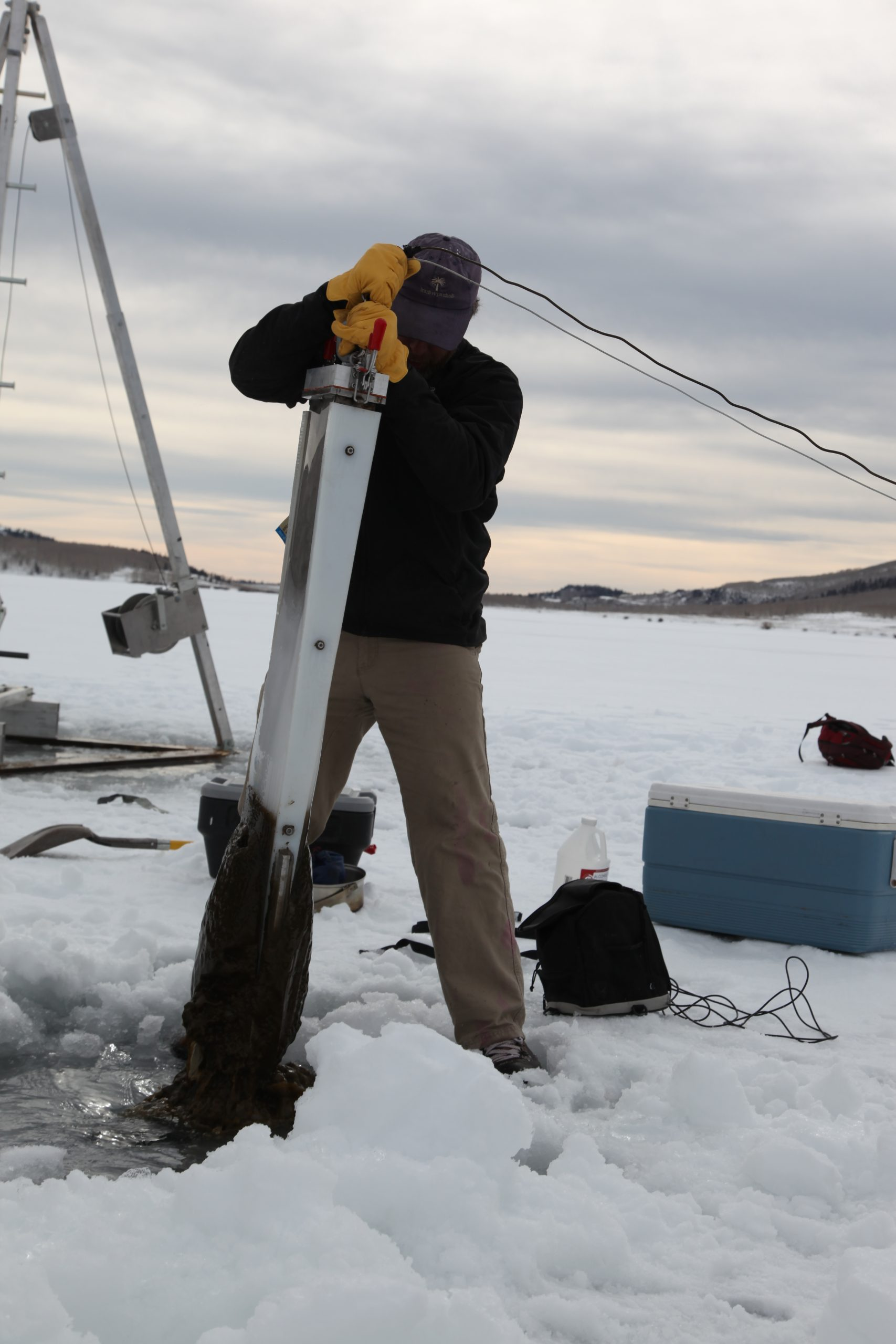 A male science in a black fleece and brown pants, pulls out an ice corer from the lake, a long cylindrical object with mud on the end.