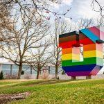 Block U sculpture on University of Utah campus is wrapped in pride flag rainbow colors on grassy hillside