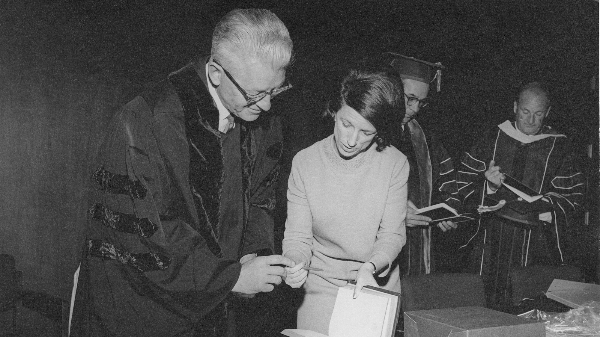 black and white image of Wallace Stegner signing a book at the library's dedication in 1960