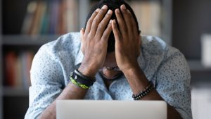 stock photo of a Black man dejected in front of a computer, with his head in his hands. Wearing a white button up shirt with blue polka dots, and wearing multiple bracelets on each wrist.