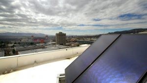 solar panel on a rooftop with University of Utah campus buildings and football stadium in background