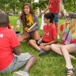 "group of kids and student leaders sit on the grass. kids all wearing red ""Club U"" t-shirts."
