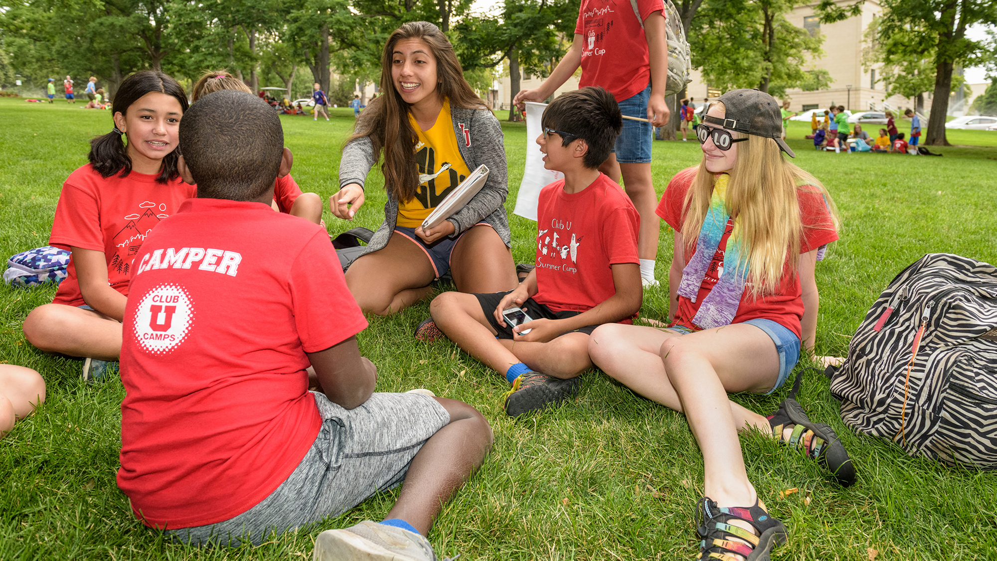 """group of kids and student leaders sit on the grass. kids all wearing red """"Club U"""" t-shirts."""