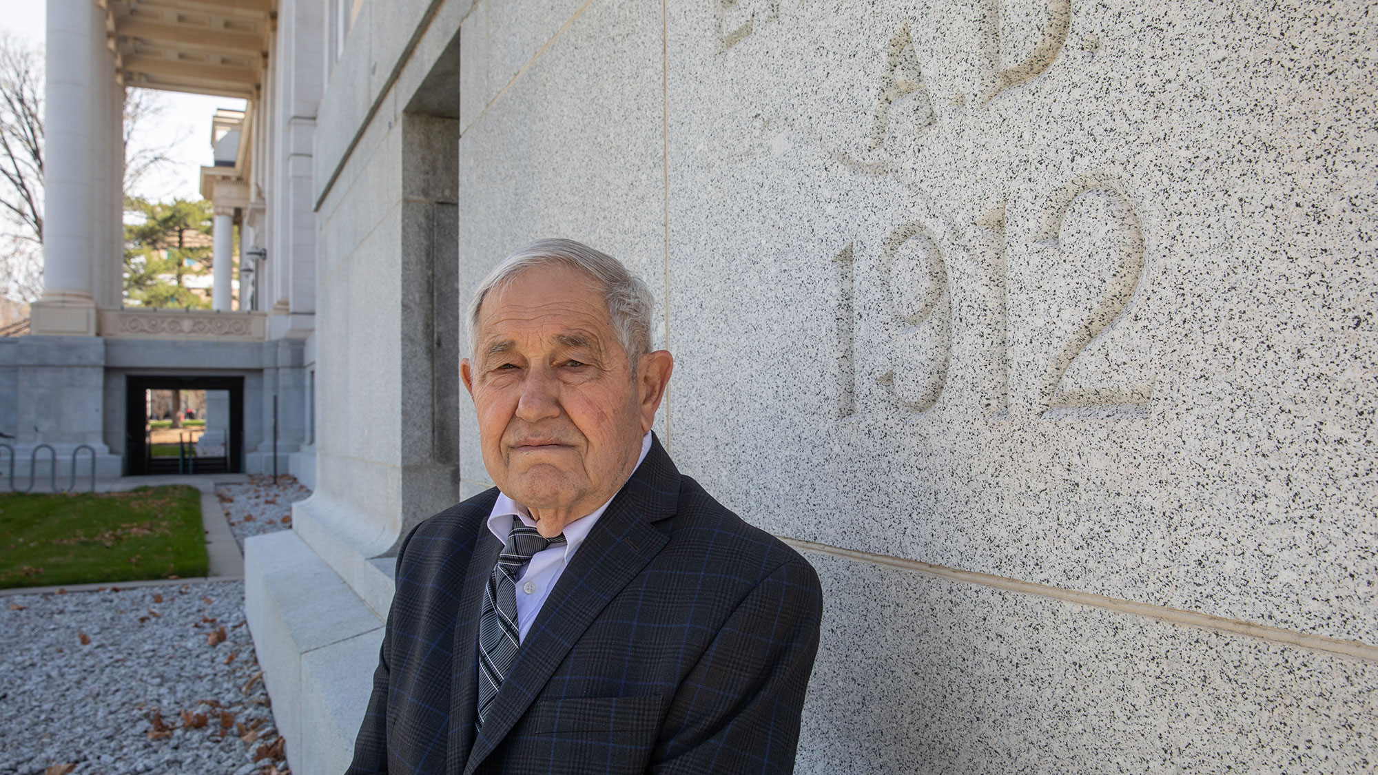 Photo of Demetrius Kourtides, a man in his 80s, leaning against a wall with partially shown 1912 carved into the outside of the building. He's wearing a black suit jacket with a blue tartan tie.