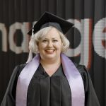 """Kirsten Caron stands in graduation cap and robe with black banner background which reads, """"change"""""""