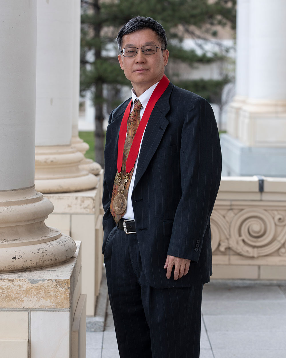 A man stands for a headshot under grecian style columns, wearing a black suit, a white shirt, glasses, and a brass medal attached to a red cloth that he's wearing around his neck.