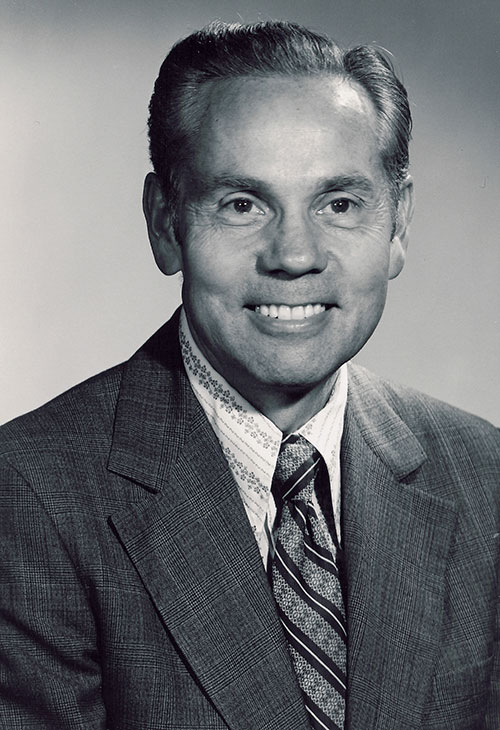 A black and white headshot of a man wearing a tweed suit jacket a striped tie and a striped, white shirt.