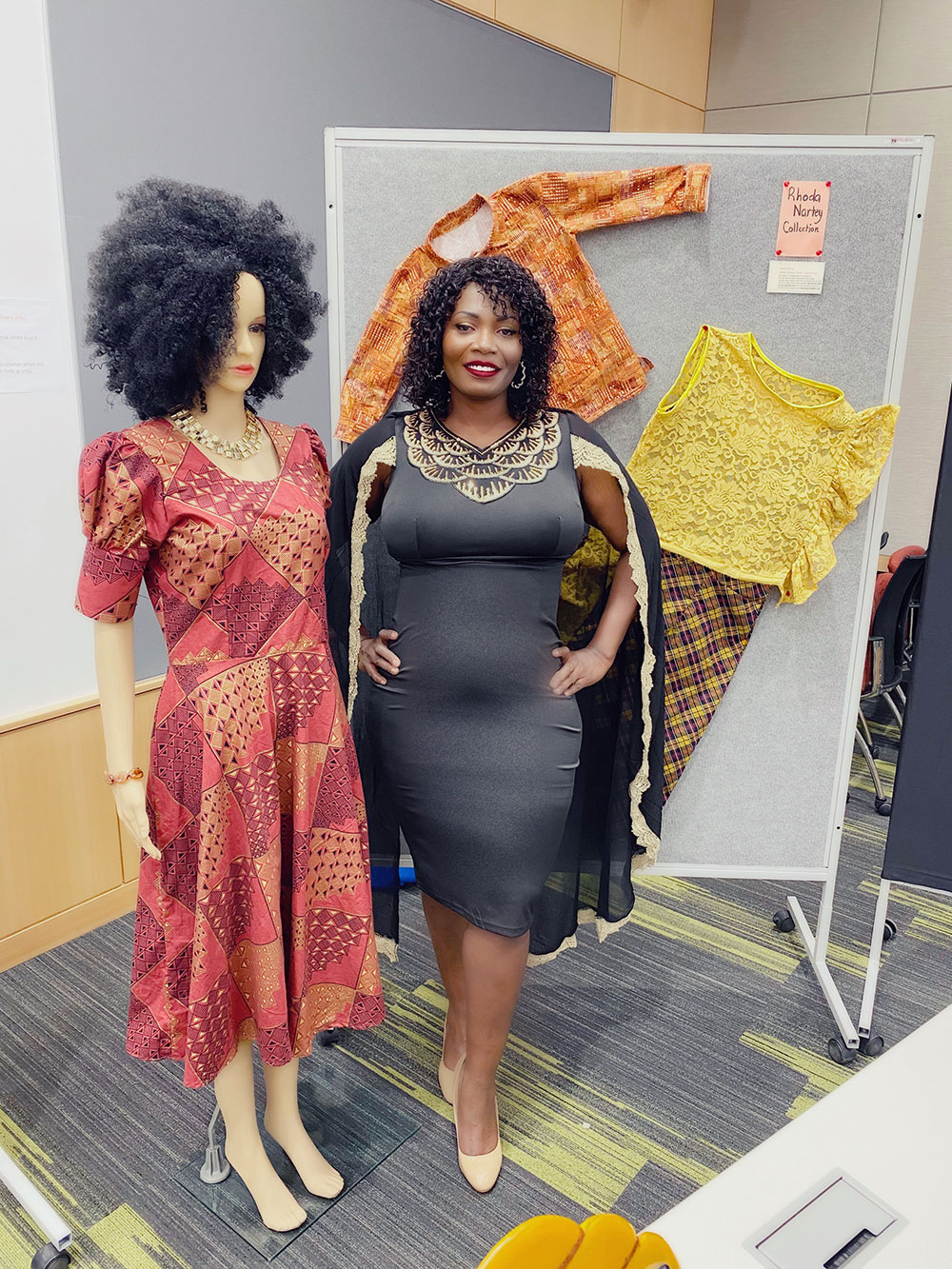 Janice Darko stands next to a mannequin that is wearing an afro wig, and wearing a red dress with an African pattern.