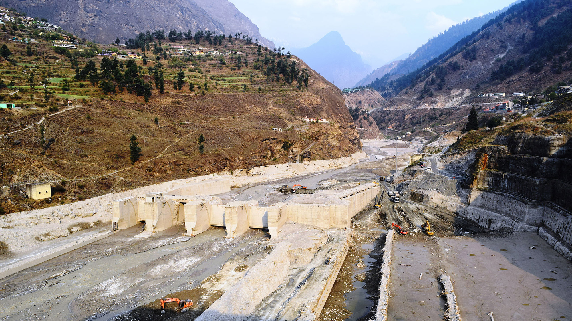 A hydoelectric dam is damaged, nestled in the Himalayan mountain scape.