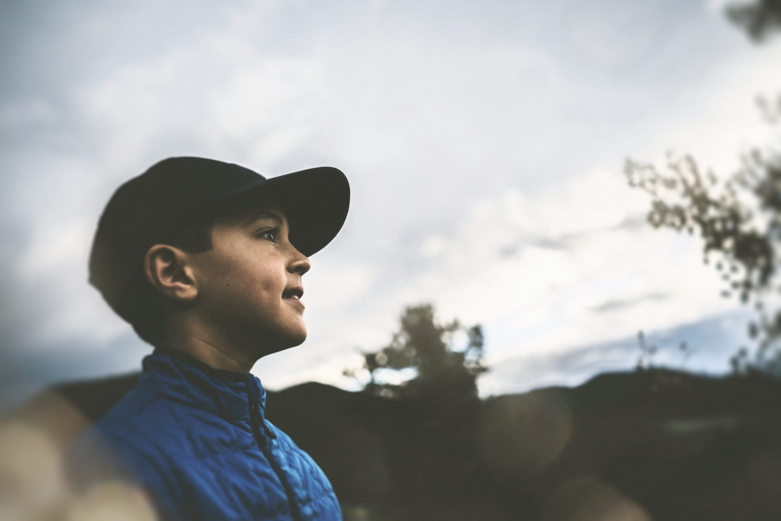 A young pre-teen who is male presenting wears a black baseball cap and a blue down jacket is at the left of the frame, lookin across to the right of the frame. He has dimples. The background is an outdoor scene of hills and two oak trees out of focus.