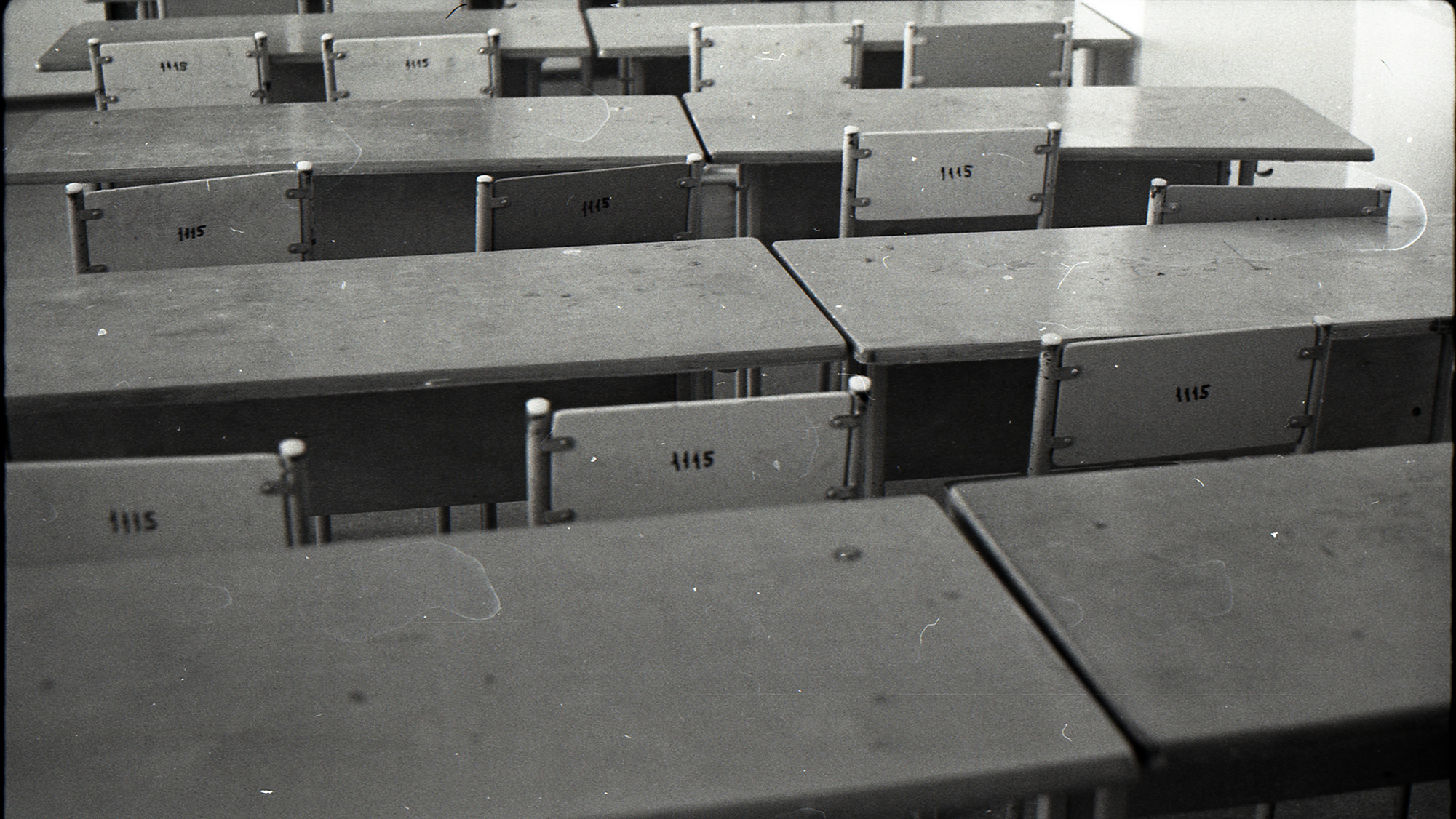 black and white photo of empty, wooden desks and chairs set up in rows in a classroom.