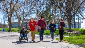 Wide photograph taken outside on the University of Utah campus of five students on a sidewalk. Four students are walking while communicating in sign language and one student is using a wheelchair.