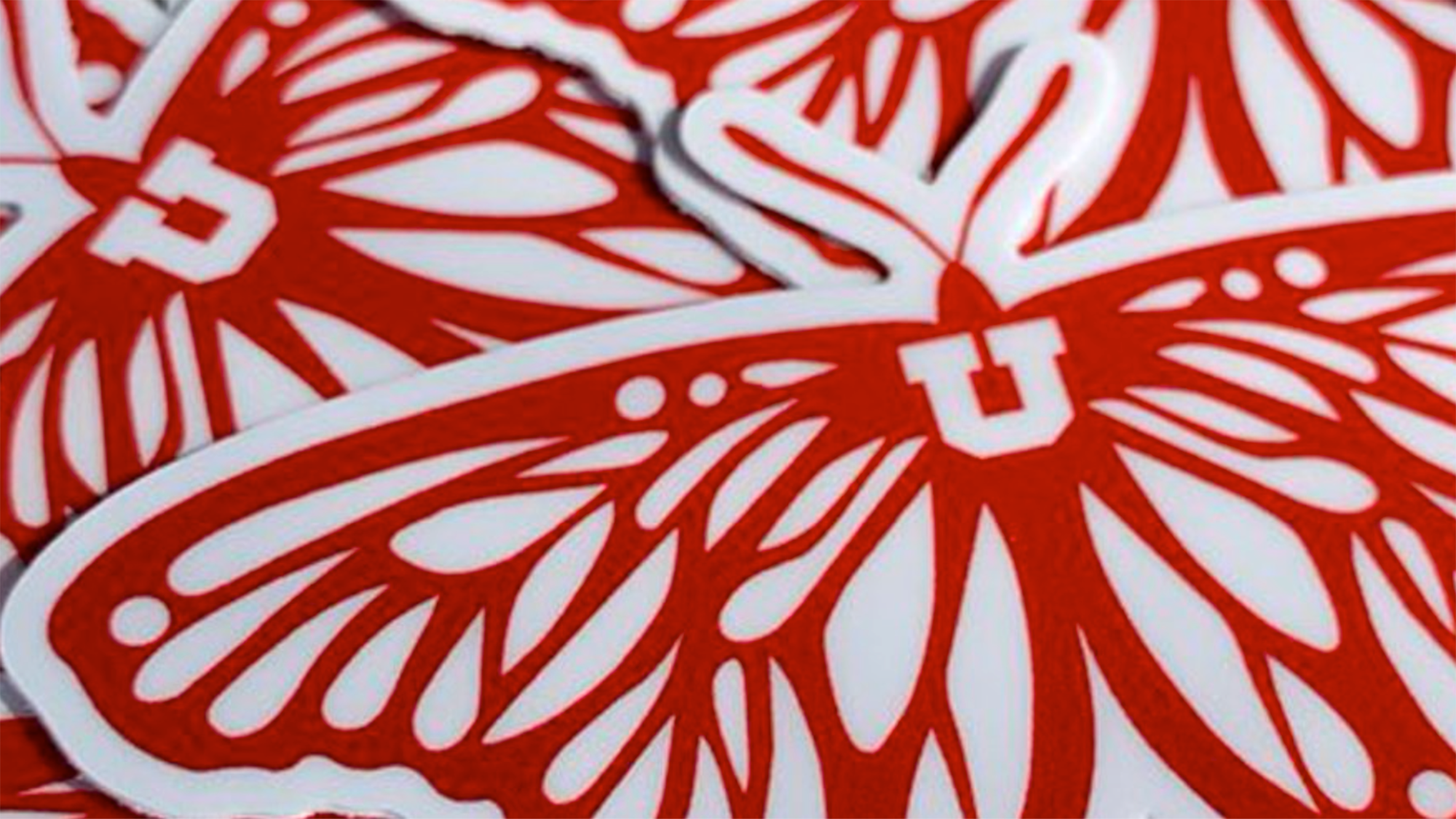 """closeup photo of a pile of stickers featuring the red butterfly with a block """"U"""" which is the Dream Center's logo."""